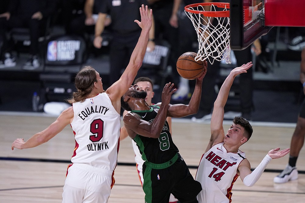 Boston Celtics guard Kemba Walker (8) takes a shot between Miami Heat's Kelly Olynyk (9) and Tyler Herro (14) during the second half of an NBA conference final playoff basketball game, Thursday, Sept. 17, 2020, in Lake Buena Vista, Fla. (AP Photo/Mark J. Terrill)