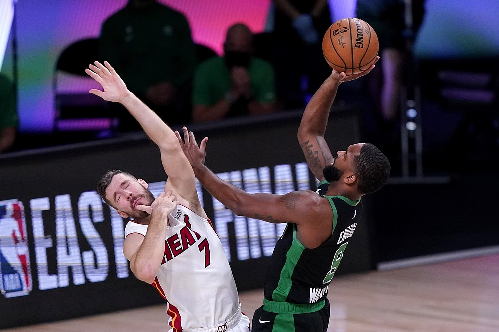 Miami Heat guard Goran Dragic (7) is knocked backwards on a shot attempt by Boston Celtics guard Brad Wanamaker (9) during the first half of an NBA conference final playoff basketball game, Thursday, Sept. 17, 2020, in Lake Buena Vista, Fla. (AP Photo/Mark J. Terrill)