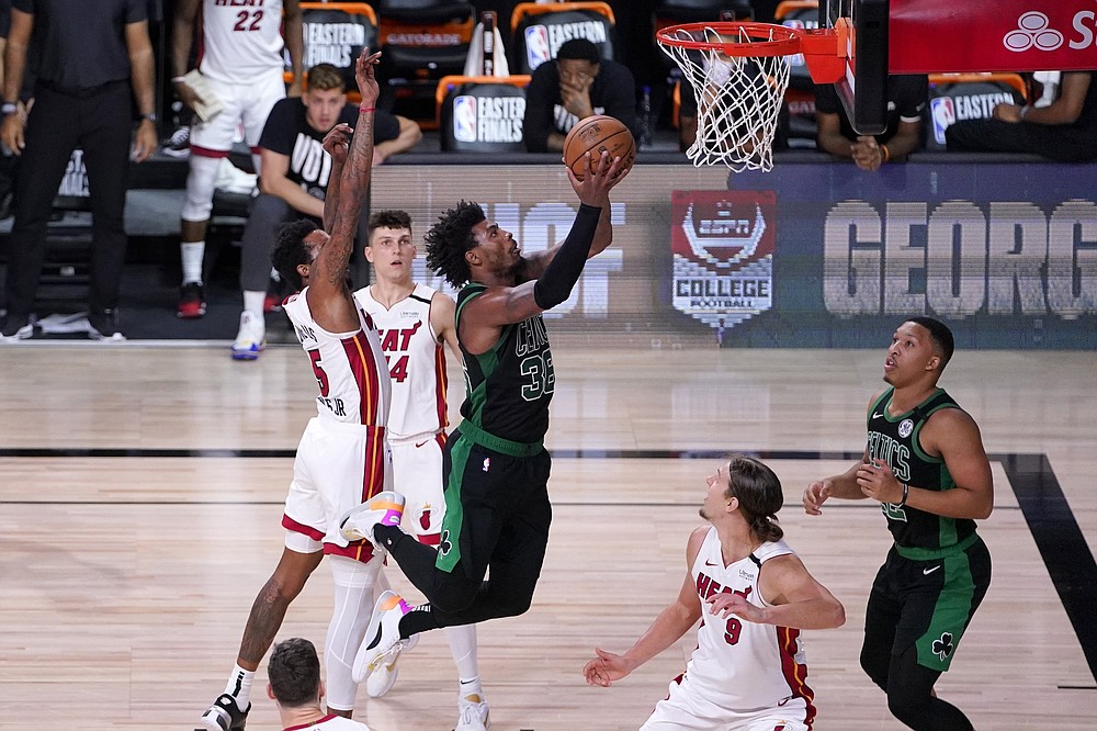 Boston Celtics guard Marcus Smart (36) goes up for a shot as Miami Heat's Derrick Jones Jr., left, Kelly Olynyk (9) and Tyler Herro (14) defend during the second half of an NBA conference final playoff basketball game, Thursday, Sept. 17, 2020, in Lake Buena Vista, Fla. The Celtics' Grant Williams, right, looks on at the play. (AP Photo/Mark J. Terrill)