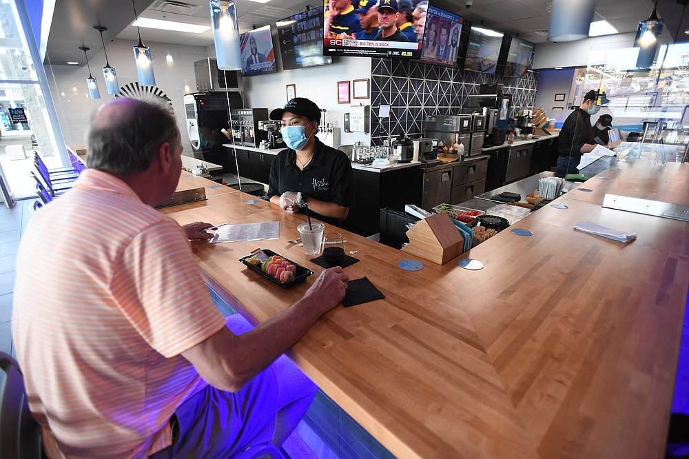 Doc Beahm of Eureka Springs orders lunch Wednesday Sept. 16,2020 from server Kochthipphan Robinson at the Hissho Sushi and Craft Beer Bar located in the Walmart store at Pleasant Crossing in Rogers. (NWA Democrat-Gazette/J.T.WAMPLER)