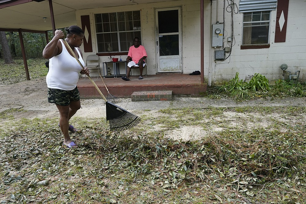 Mamie Patterson helps her cousin Kenneth Bargaineer, right, clean up after Hurricane Sally, Friday, Sept. 18, 2020, in Pensacola, Fla. (AP Photo/Gerald Herbert)