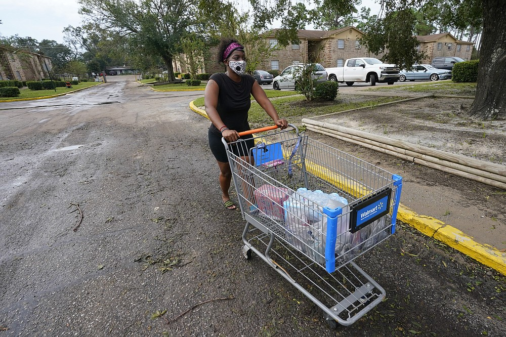 Fanchiskia Gulley moves toward her apartment after purchasing provisions in the aftermath of Hurricane Sally, Friday, Sept. 18, 2020, in Fla. (AP Photo/Gerald Herbert)