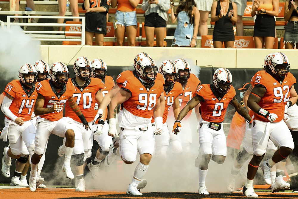 Oklahoma State players take the field before an NCAA college football game against Tulsa, Saturday, Sept. 19, 2020, in Stillwater, Okla. (AP Photo/Brody Schmidt)