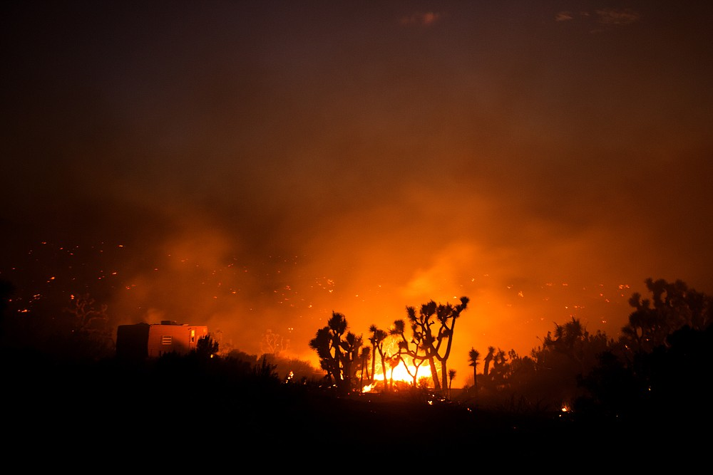 A recreational vehicle sits at left as the Bobcat Fire burns in Juniper Hills, Calif., Friday, Sept. 18, 2020. (AP Photo/Ringo H.W. Chiu)