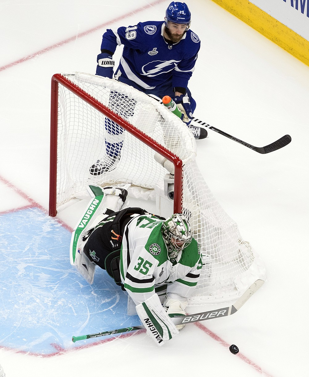 Dallas Stars goaltender Anton Khudobin (35) makes a save as Tampa Bay Lightning left wing Barclay Goodrow (19) looks for the puck during second-period NHL Stanley Cup finals hockey action in Edmonton, Alberta, Saturday, Sept. 19, 2020. (Jason Franson/The Canadian Press via AP)