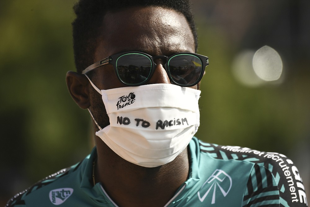 """France's Kevin Reza wears a face mask reading """"No To Racism"""" as he arrives for the start of the twenty-first and last stage of the Tour de France cycling race over 122 kilometers (75.8 miles), from Mantes-La-Jolie to Paris, France, Sunday, Sept. 20, 2020. (Marco Bertorello/Pool via AP)"""
