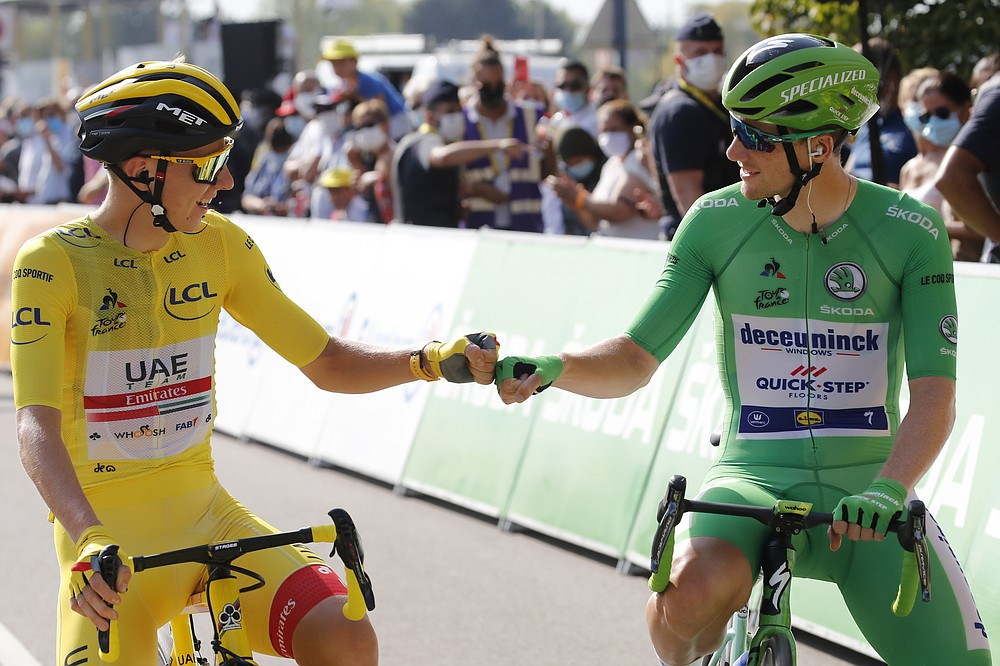 Slovenia's Tadej Pogacar, wearing the overall leader's yellow jersey, greets Sam Bennett of Ireland, wearing the best sprinter's green jersey, prior to the twenty-first and last stage of the Tour de France cycling race over 122 kilometers (75.8 miles), from Mantes-La-Jolie to Paris, France, Sunday, Sept. 20, 2020. (AP Photo/Christophe Ena)