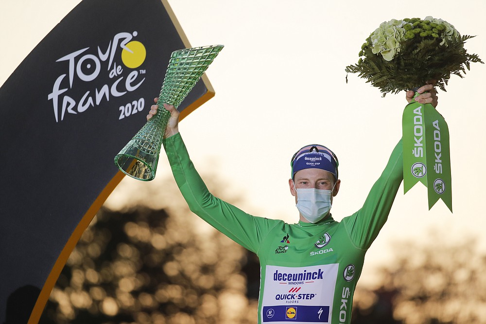 Sam Bennett of Ireland, wearing the best sprinter's green jersey, celebrates on the podium after the twenty-first and last stage of the Tour de France cycling race over 122 kilometers (75.8 miles), from Mantes-la-Jolie to Paris, France, Sunday, Sept. 20, 2020. (AP Photo/Christophe Ena)