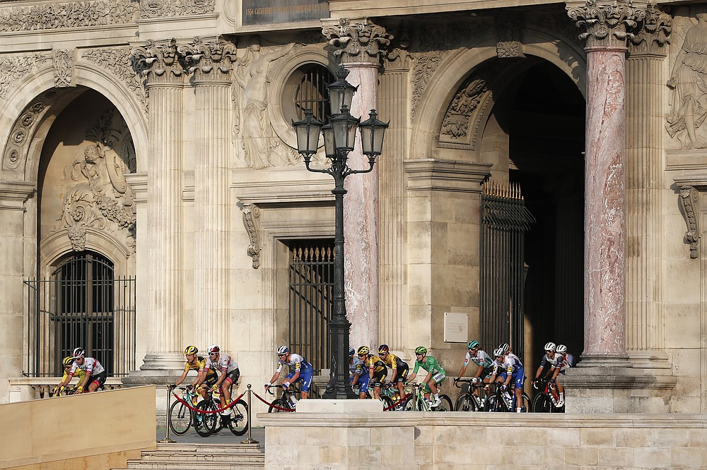 The pack arrives in the courtyard of the Louvre museum during the 122 kilometers (75.8 miles) final stage of the Tour de France cycling race between Mantes-la-Jolie and Paris, Sunday Sept. 20, 2020 in Paris. (AP Photo/Francois Mori, Pool)