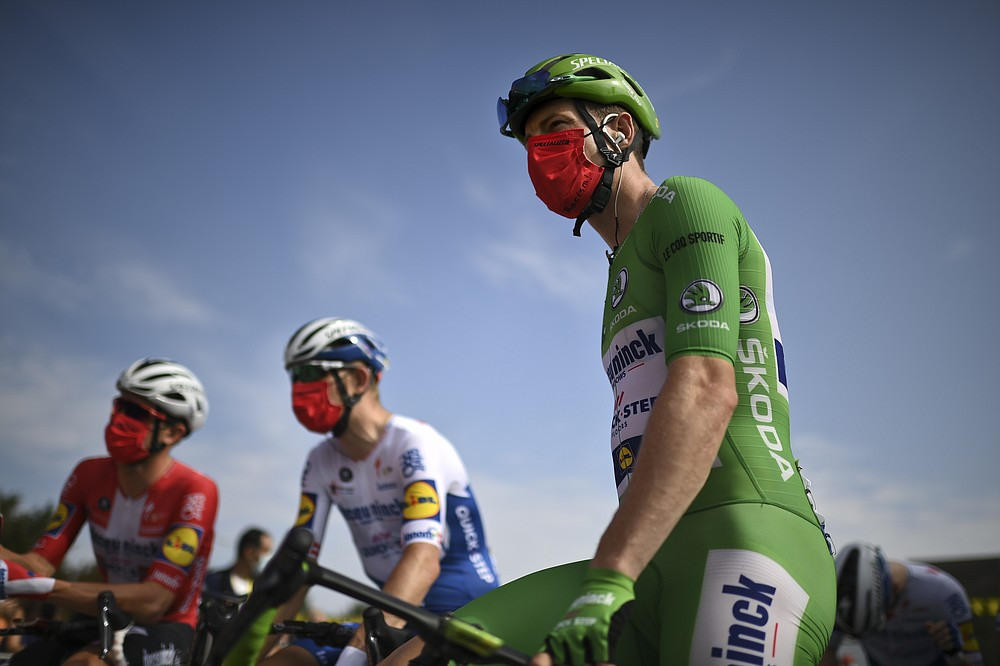 """Sam Bennett of Ireland, wearing the best sprinter's green jersey, wears a face mask reading """"No To Racism"""" as he arrives for the start of the twenty-first and last stage of the Tour de France cycling race over 122 kilometers (75.8 miles), from Mantes-La-Jolie to Paris, France, Sunday, Sept. 20, 2020. (Marco Bertorello/Pool via AP)"""