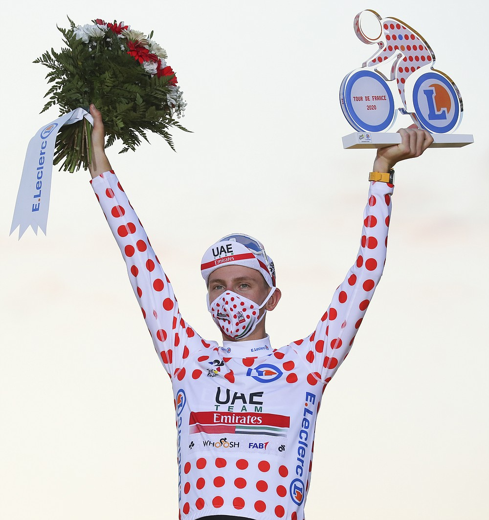 Tour de France winner Slovenia's Tadej Pogacar, who also won the best climber's dotted jersey, celebrates on the podium after the twenty-first and last stage of the Tour de France cycling race over 122 kilometers (75.8 miles), from Mantes-la-Jolie to Paris, France, Sunday, Sept. 20, 2020. (AP Photo/Thibault Camus)