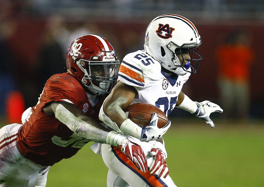 FILE - In this Nov. 24, 2018, file photo, Auburn running back Shaun Shivers (25) is tackled by Alabama linebacker Dylan Moses (32) during the second half of an NCAA college football game in Tuscaloosa, Ala. The Tide opens next Saturday at Missouri with Moses returning when he might otherwise have left for the NFL. (AP Photo/Butch Dill, File)