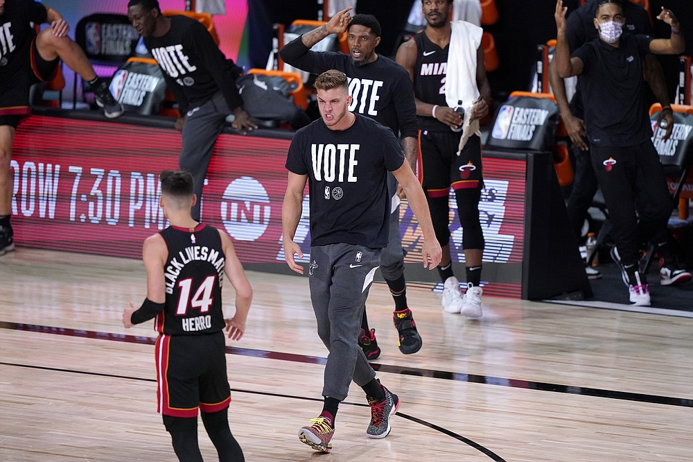 Miami Heat's Meyers Leonard, center, runs onto the court during a time out to celebrate with Tyler Herro (14) after Herro's 3-point basket against the Boston Celtics in the first half of an NBA conference final playoff basketball game, Saturday, Sept. 19, 2020, in Lake Buena Vista, Fla. (AP Photo/Mark J. Terrill)