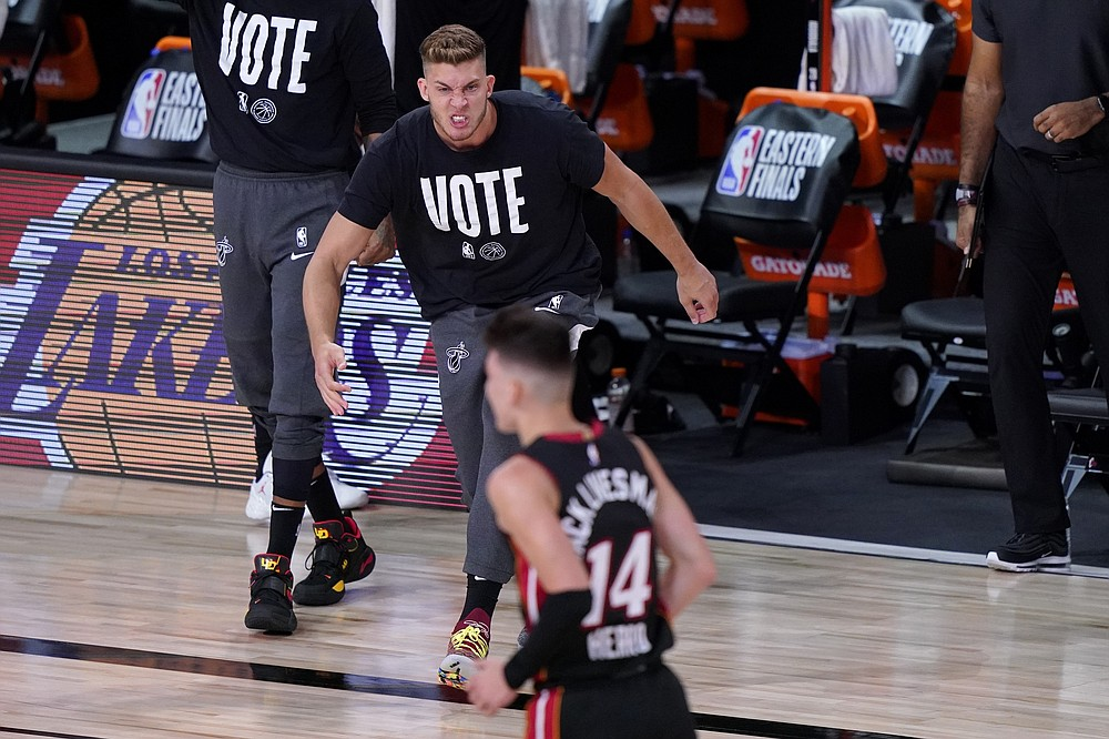 Miami Heat's Meyers Leonard, top, runs onto the court during a time out to celebrate with Tyler Herro (14) after Herro's 3-point basket against the Boston Celtics in the first half of an NBA conference final playoff basketball game, Saturday, Sept. 19, 2020, in Lake Buena Vista, Fla. (AP Photo/Mark J. Terrill)