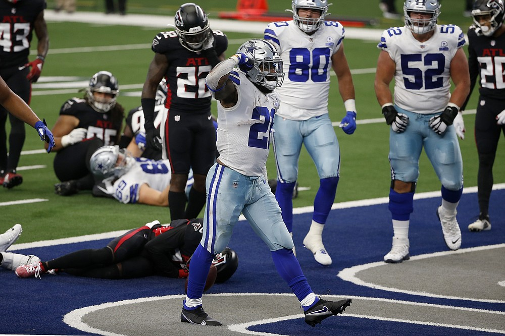 Dallas Cowboys running back Ezekiel Elliott (21) celebrates running the ball for a touchdown as Atlanta Falcons' Keanu Neal (22) checks on injured teammate Damontae Kazee, bottom, in the first half of an NFL football game in Arlington, Texas, Sunday, Sept. 20, 2020. (AP Photo/Ron Jenkins)