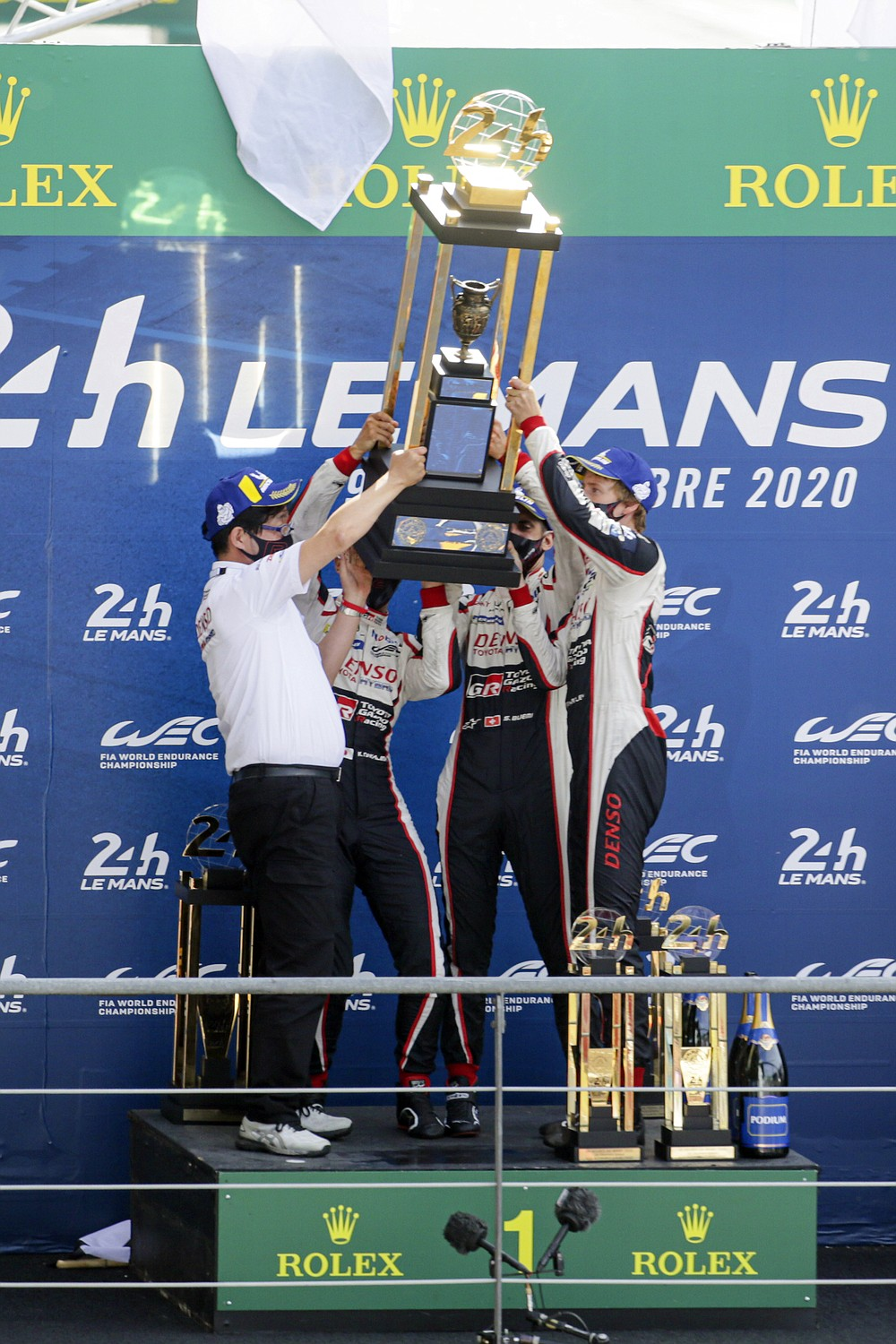 The Toyota TS050 Hybrid No8 of the Toyota Gazoo Racing Team's drivers Sebastien Buemi of Switzerland, Kazuki Nakajima of Japan and Brendon Hartley hold the trophy during the podium ceremony of the 88th 24-hour Le Mans endurance race, in Le Mans, western France, Sunday, Sept. 20, 2020. (AP Photo/David Vincent)