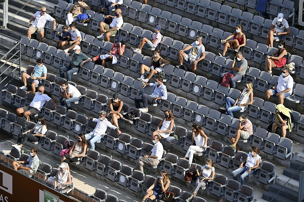 Spectators sit respecting social distance to limit the spread of COVID-19 as Norway's Casper Ruud rplays Serbia's Novak Đjoković during their semifinal at the Italian Open tennis tournament, in Rome, Sunday, Sept. 20, 2020. (Alfredo Falcone/LaPresse via AP)
