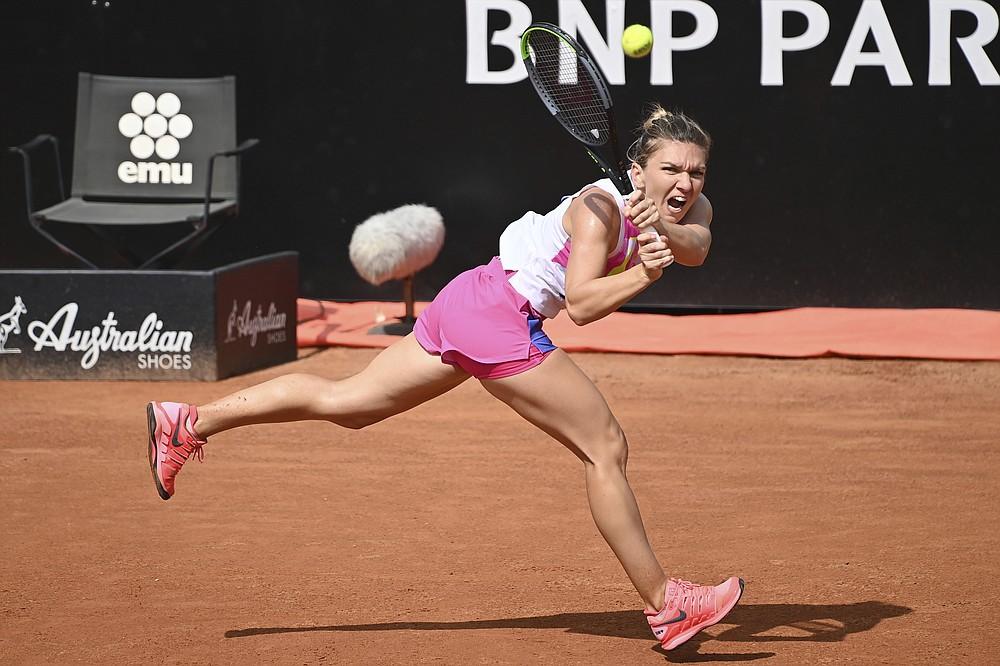 Romania's Simona Halep returns the ball to Spain's Garbine Muguruza during their semifinal at the Italian Open tennis tournament, in Rome, Sunday, Sept. 20, 2020. (Alfredo Falcone/LaPresse via AP)