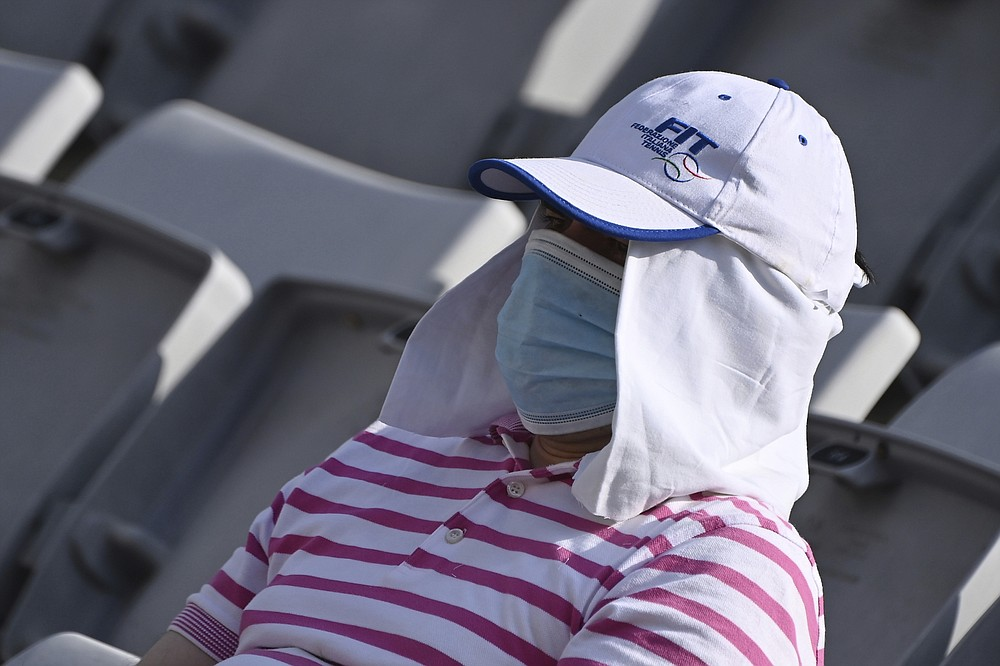 A spectator wears a face mask to protect against COVID-19 contagion during the semifinal match between Spain's Garbine Muguruza and Romania's Simona Halep, at the Italian Open tennis tournament, in Rome, Sunday, Sept. 20, 2020. (Alfredo Falcone/LaPresse via AP)