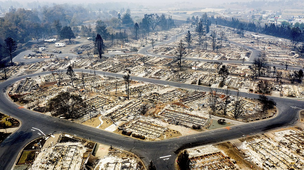 FILE - In this photo taken by a drone, homes leveled by the Almeda Fire line the Bear Lake Estates in Phoenix, Ore., Tuesday, Sept. 15, 2020.  The Census Bureau is contending with several natural disasters as wildfires and hurricanes disrupt the final weeks of the nation's once-a-decade headcount. (AP Photo/Noah Berger)
