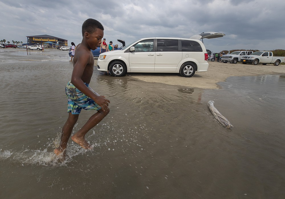 Lyrick Gipson, 9, races through the flooding Stewart Beach parking lot in Galveston, Texas on Saturday, Sept. 19, 2020. Tropical Storm Beta continues to move through the Gulf of Mexico and is expected to bring tidal surge and heavy rain to the area.  (Stuart Villanueva/The Galveston County Daily News via AP)