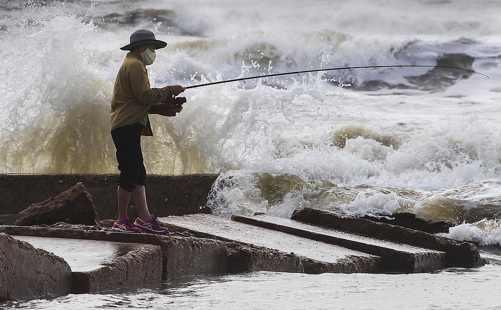 Waves crash as Houston resident Tinh Pham fishes from the rocks at Diamond Beach on the west end of the Galveston Seawall in Galveston, Texas on Saturday, Sept. 19, 2020. Tropical Storm Beta continues to move through the Gulf of Mexico and is expected to bring tidal surge and heavy rain to the area.  (Stuart Villanueva/The Galveston County Daily News via AP)