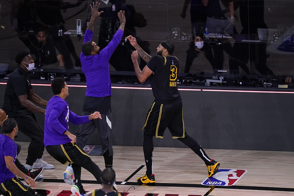 Los Angeles Lakers' Anthony Davis (3) celebrates with teammates after making a 3-point basket at the end of an NBA conference final playoff basketball game against the Denver Nuggets Sunday, Sept. 20, 2020, in Lake Buena Vista, Fla. The Lakers won 105-103. (AP Photo/Mark J. Terrill)