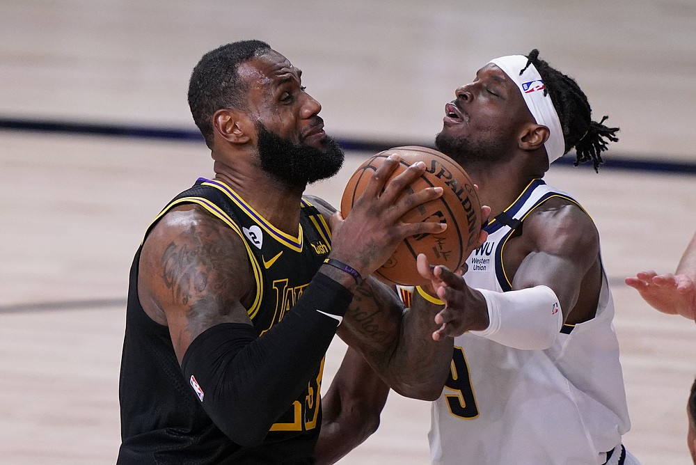 Los Angeles Lakers' LeBron James, left, drives to the basket over Denver Nuggets' Jerami Grant (9) during the second half of an NBA conference final playoff basketball game Sunday, Sept. 20, 2020, in Lake Buena Vista, Fla. (AP Photo/Mark J. Terrill)