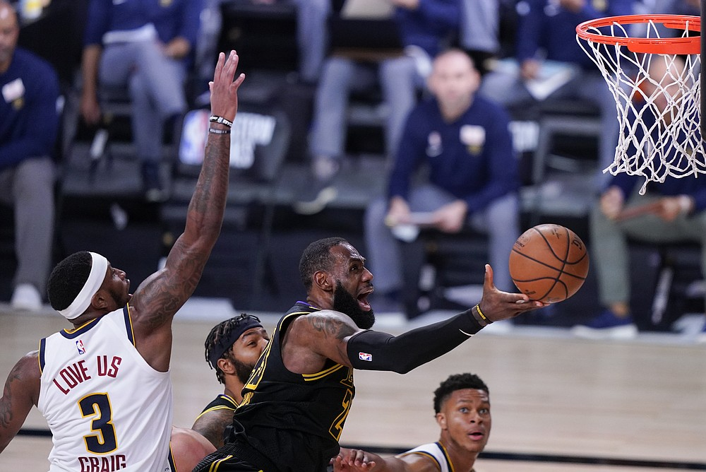 Los Angeles Lakers' LeBron James drives to the basket ahead of Denver Nuggets' Torrey Craig (3) during the second half of an NBA conference final playoff basketball game Sunday, Sept. 20, 2020, in Lake Buena Vista, Fla. (AP Photo/Mark J. Terrill)