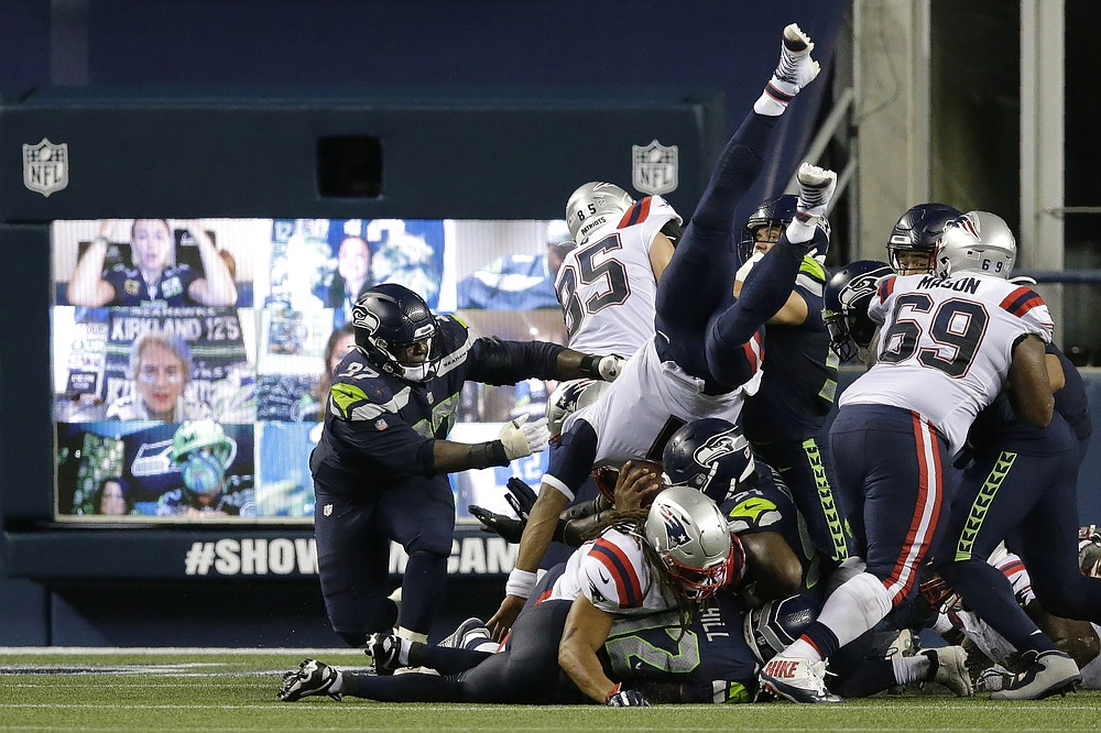 New England Patriots quarterback Cam Newton dives with the ball but is stopped near the goal line as the clock expires in the fourth quarter of an NFL football game against the Seattle Seahawks, Sunday, Sept. 20, 2020, in Seattle. The Seahawks won 35-30. In the background, fans cheer via remote video links on a video monitor. (AP Photo/John Froschauer)