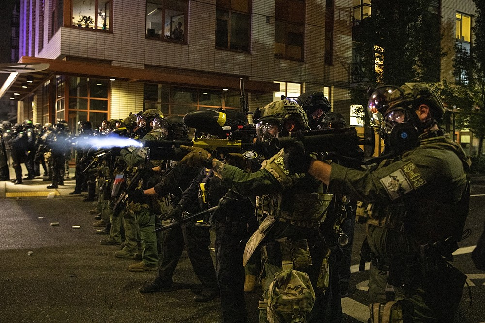 FILE - In this Friday, Sept. 18, 2020, file photo, Federal police try to take control of the streets during protests in Portland, Ore. The protests, which began over the killing of George Floyd, often result frequent clashes between protesters and law enforcement. Vandalism but no arrests occurred during a demonstration in downtown Portland involving about 200 people Saturday, Sept. 19, 2020. Frequently violent protests have racked the city for more than three months since the police killing of George Floyd in Minneapolis. Protesters want city officials to slash the police budget and reallocate money to Black residents and businesses. Some demonstrators also demand the resignation of the city's mayor. (AP Photo/Paula Bronstein, File)