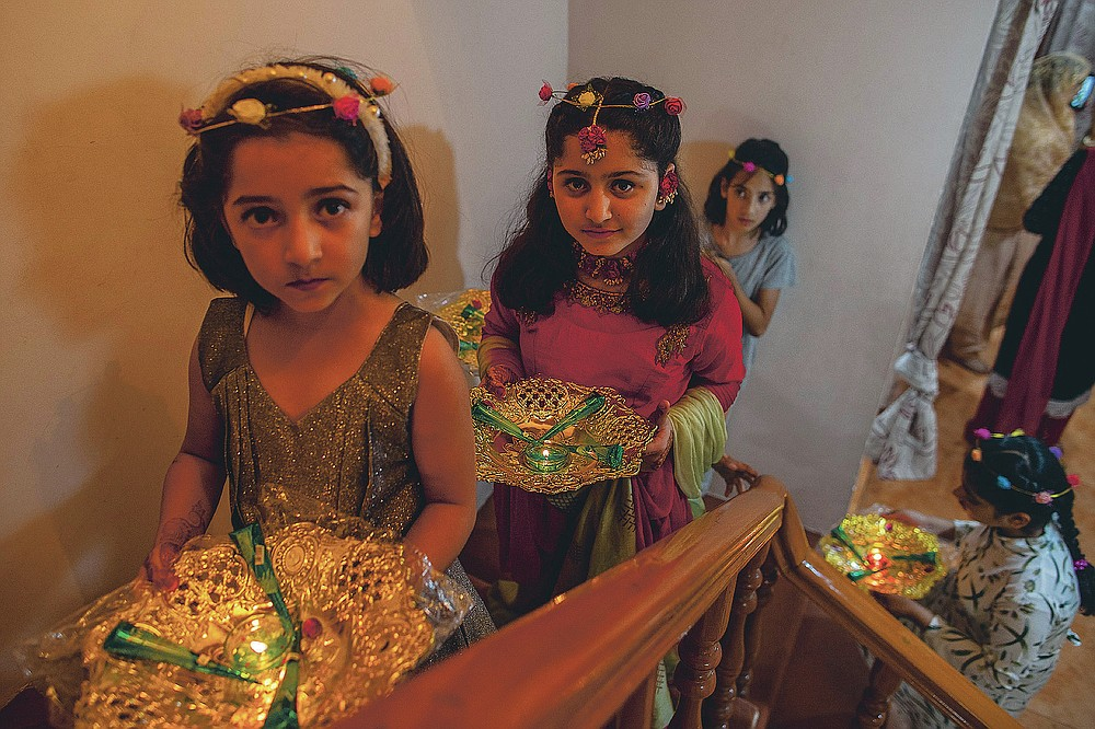 Des proches de la mariée cachemirienne portent du henné et des bougies dans un panier décoratif lors de la cérémonie au henné d'un mariage à la périphérie de Srinagar, Cachemire sous contrôle indien, le mardi 16 septembre 2020. La pandémie de coronavirus a changé la façon dont les gens célèbrent les mariages au Cachemire. Les festivités traditionnelles d'une semaine, les rituels élaborés et les grands rassemblements ont cédé la place à des cérémonies en sourdine auxquelles un nombre limité de parents proches y assistent. Avec des restrictions en place et de nombreux mariages annulés, les chefs de mariage traditionnels ont peu ou pas de travail. Le virus a considérablement affecté la vie et les entreprises de la région. (Photo AP / Dar Yasin)