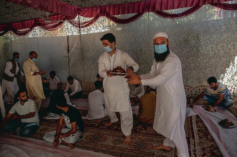 Des hommes du Cachemire portent des assiettes de riz avant de les servir aux invités lors d'une cérémonie de mariage à la périphérie de Srinagar, Cachemire sous contrôle indien, le vendredi 18 septembre 2020. La pandémie de coronavirus a changé la façon dont les gens célèbrent les mariages au Cachemire. Les festivités traditionnelles d'une semaine, les rituels élaborés et les grands rassemblements ont cédé la place à des cérémonies en sourdine auxquelles un nombre limité de parents proches y assistent. Avec des restrictions en place et de nombreux mariages annulés, les chefs de mariage traditionnels ont peu ou pas de travail. Le virus a considérablement affecté la vie et les entreprises de la région. (Photo AP / Dar Yasin)