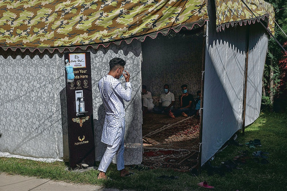 Umar Fayaz, un garçon cachemirien porte un masque avant d'entrer dans une tente lors d'un mariage à la périphérie de Srinagar, Cachemire sous contrôle indien, le jeudi 17 septembre 2020. La pandémie de coronavirus a changé la façon dont les gens célèbrent les mariages au Cachemire. Les festivités traditionnelles d'une semaine, les rituels élaborés et les grands rassemblements ont cédé la place à des cérémonies en sourdine auxquelles un nombre limité de parents proches y assistent. Avec des restrictions en place et de nombreux mariages annulés, les chefs de mariage traditionnels ont peu ou pas de travail. Le virus a considérablement affecté la vie et les entreprises de la région. (Photo AP / Dar Yasin)