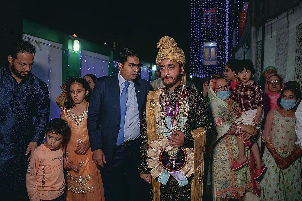 Des proches et des voisins marchent avec Haseeb Mushtaq, un marié cachemirien lors de sa cérémonie de mariage à la périphérie de Srinagar, au Cachemire sous contrôle indien, le lundi 14 septembre 2020. La pandémie de coronavirus a changé la façon dont les gens célèbrent les mariages au Cachemire. Les festivités traditionnelles d'une semaine, les rituels élaborés et les grands rassemblements ont cédé la place à des cérémonies en sourdine auxquelles un nombre limité de parents proches y assistent. Avec des restrictions en place et de nombreux mariages annulés, les chefs de mariage traditionnels ont peu ou pas de travail. Le virus a considérablement affecté la vie et les entreprises de la région. (Photo AP / Dar Yasin)