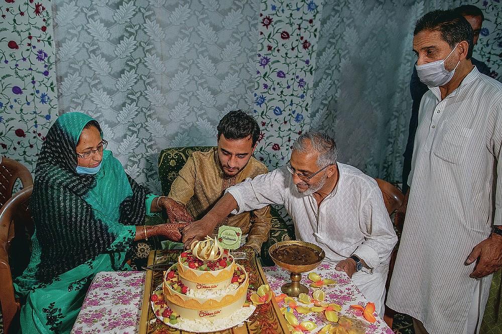 Haseeb Mushtaq, au centre, un marié cachemirien avec ses parents ont coupé le gâteau lors d'une cérémonie au henné d'un mariage à la périphérie de Srinagar, Cachemire sous contrôle indien, dimanche 13 septembre 2020. La pandémie de coronavirus a changé la façon dont les gens célèbrent les mariages au Cachemire. Les festivités traditionnelles d'une semaine, les rituels élaborés et les grands rassemblements ont cédé la place à des cérémonies en sourdine auxquelles un nombre limité de parents proches y assistent. Avec des restrictions en place et de nombreux mariages annulés, les chefs de mariage traditionnels ont peu ou pas de travail. Le virus a considérablement affecté la vie et les entreprises de la région. (Photo AP / Dar Yasin)