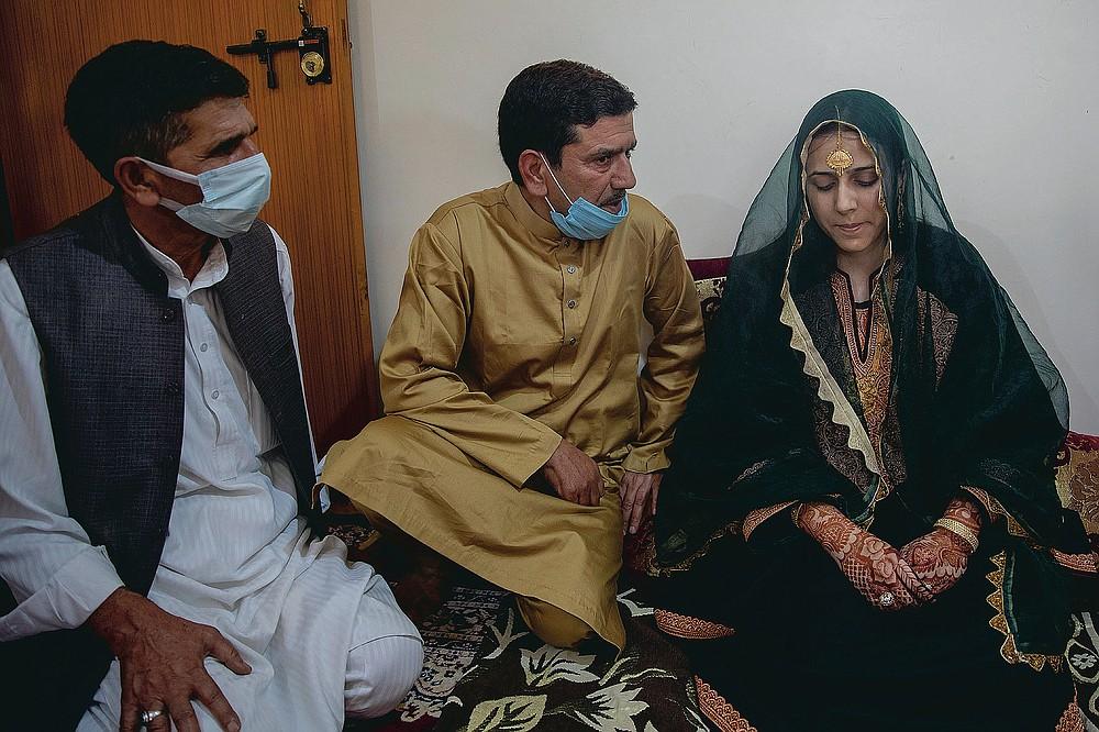 Fayaz Ahmed, au centre et Manor Ahmed, à gauche, les oncles de l'épouse cachemirienne Saima Ashraf, lui demandent la permission avant la cérémonie de Nikah lors d'un mariage à la périphérie de Srinagar, Cachemire sous contrôle indien, le jeudi 17 septembre 2020. La pandémie de coronavirus a changé la façon dont les gens célèbrent les mariages au Cachemire. Les festivités traditionnelles d'une semaine, les rituels élaborés et les grands rassemblements ont cédé la place à des cérémonies en sourdine auxquelles un nombre limité de parents proches y assistent. Avec des restrictions en place et de nombreux mariages annulés, les chefs de mariage traditionnels ont peu ou pas de travail. Le virus a considérablement affecté la vie et les entreprises de la région. (Photo AP / Dar Yasin)