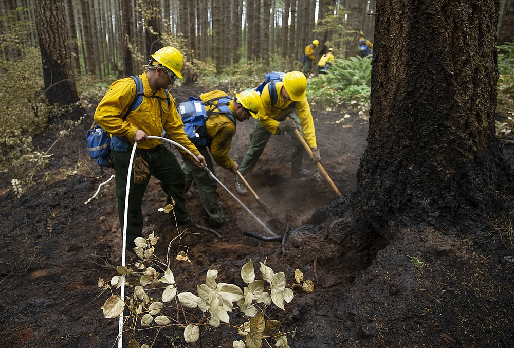 A fire crew from the Oregon Air National Guard douses hot spots on the fire lines of the Holiday Farm Fire, east of Springfield, Ore., Monday Sept. 21, 2020. (Chris Pietsch/The Register-Guard via AP)