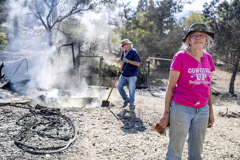 Cheryl Poindexter returns to her property on Monday, Sept. 21, 2020 after the Bobcat fire burned her home of 27 years and the 11 acre property where she ran an animal rescue in Juniper Hills, Calif. as her friend Dale Burton, of Leona Valley, tries to put out the fire that continues to smolder in her septic. (Sarah Reingewirtz/The Orange County Register via AP)