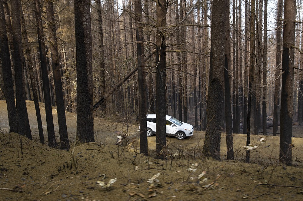 A vehicle moves through a burned area of the Holiday Farm Fire, east of Springfield, Ore., Monday Sept. 21, 2020. (Chris Pietsch/The Register-Guard via AP)