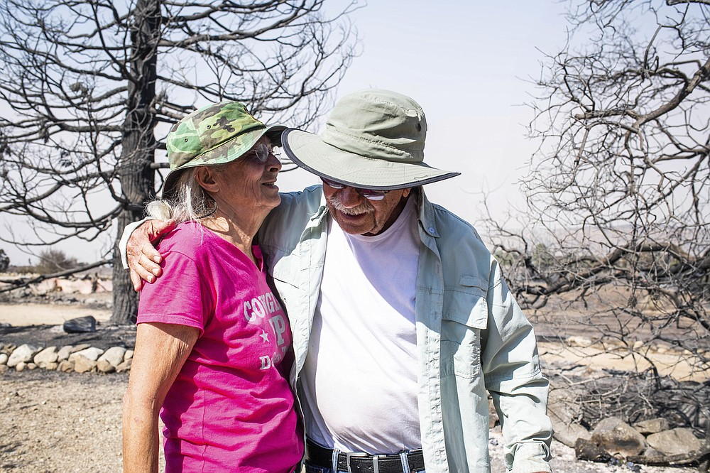 Robert Wise hugs on Monday, Sept. 21, 2020 his neighbor Cheryl Poindexter, who lost her home of 27 in the Bobcat fire. Poindexter ran an animal rescue on her 11 acres along Juniper Hills Road. (Sarah Reingewirtz/The Orange County Register via AP)