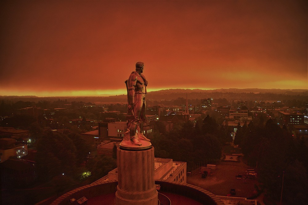 "This drone photo provided by Michael Mann shows the Oregon Capitol building, with its ""Oregon Pioneer"" bronze sculpture atop the dome, with skies filled with smoke and ash from wildfires as a backdrop in Salem, Ore., on Sept. 8, 2020. Fires continued to rage across the West Coast on Monday, Sept. 21, 2020. (Michael Mann via AP)"