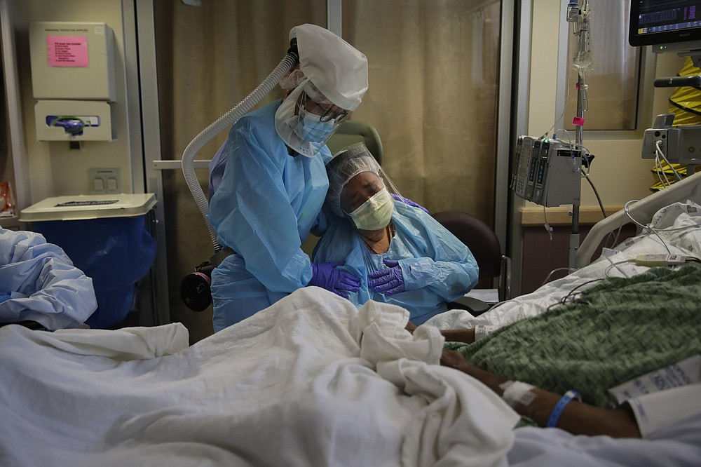 FILE - In this July 31, 2020, file photo, Romelia Navarro, right, is comforted by nurse Michele Younkin as she weeps while sitting at the bedside of her dying husband, Antonio, in St. Jude Medical Center's COVID-19 unit in Fullerton, Calif. The U.S. death toll from the coronavirus topped 200,000 Tuesday, Sept. 22, a figure unimaginable eight months ago when the scourge first reached the world's richest nation with its sparkling laboratories, top-flight scientists and towering stockpiles of medicines and emergency supplies. (AP Photo/Jae C. Hong, File)