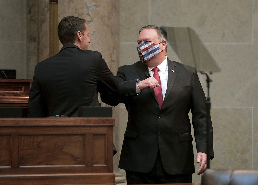 Secretary of State Mike Pompeo , right, is greeted by Wisconsin Senate President Roger Roth, R-Appleton, during a speaking engagement with state Republican legislators in the Senate chamber of the Wisconsin State Capitol in Madison, Wis. Wednesday, Sept. 23, 2020. (John Hart/Wisconsin State Journal via AP)