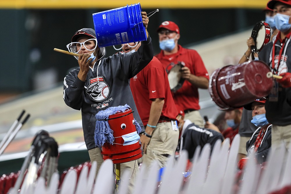 Members of the Reds' grounds crew acknowledge Cincinnati Reds' Trevor Bauer as he stands in the dugout in the ninth inning during a baseball game between the Milwaukee Brewers and the Cincinnati Reds in Cincinnati, Wednesday, Sept. 23, 2020. The Reds won 6-1. (AP Photo/Aaron Doster)