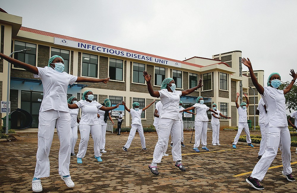FILE - In this May 17, 2020, file photo, nurses who care for coronavirus patients take part in a Zumba dance-fitness class outside of the Kenyatta University Teaching, Referral and Research Hospital in Nairobi, Kenya. The class helps them deal with the stress and difficult work. The pandemic has fractured global relationships as governments act in the interest of their citizens first, but John Nkengasong, Africa's top public health official, has helped to steer the continent's 54 countries into an alliance praised as responding better than some richer nations. (AP Photo/Brian Inganga, File)