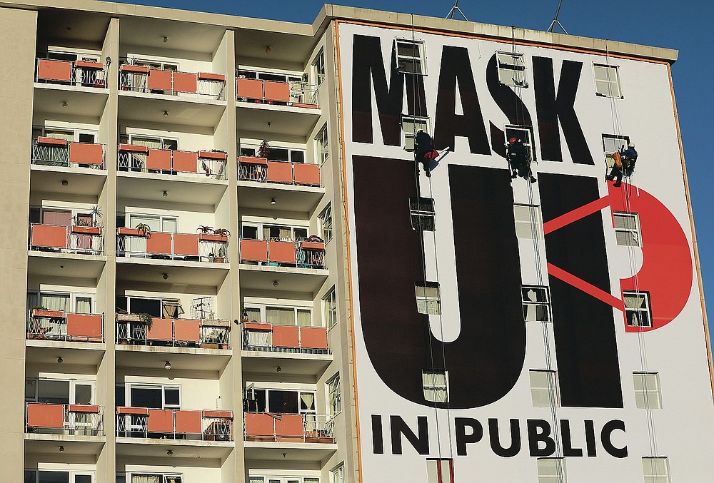 FILE - In this May 16, 2020, file photo, a billboard is installed on an apartment building encouraging people to wear face masks in Cape Town, South Africa, on the 51st day of a strict government lockdown in a bid to curb the spread of the coronavirus. The pandemic has fractured global relationships as governments act in the interest of their citizens, but John Nkengasong, Africa's top public health official, has helped to steer the continent's 54 countries into an alliance praised as responding better than some richer nations. (AP Photo/Nardus Engelbrecht, File)