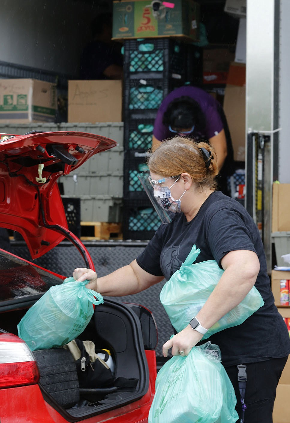 Ginger Garner, with Fayetteville Public Schools, loads Tuesday, September 22, 2020, meals into the back of a vehicle during a curbside service at Fayetteville High School. The district distributed 10 meals each to 350 students. The meals are available to all students in the district. Check out nwaonline.com/200923Daily/ and nwadg.com/photos for a photo gallery. (NWA Democrat-Gazette/David Gottschalk)