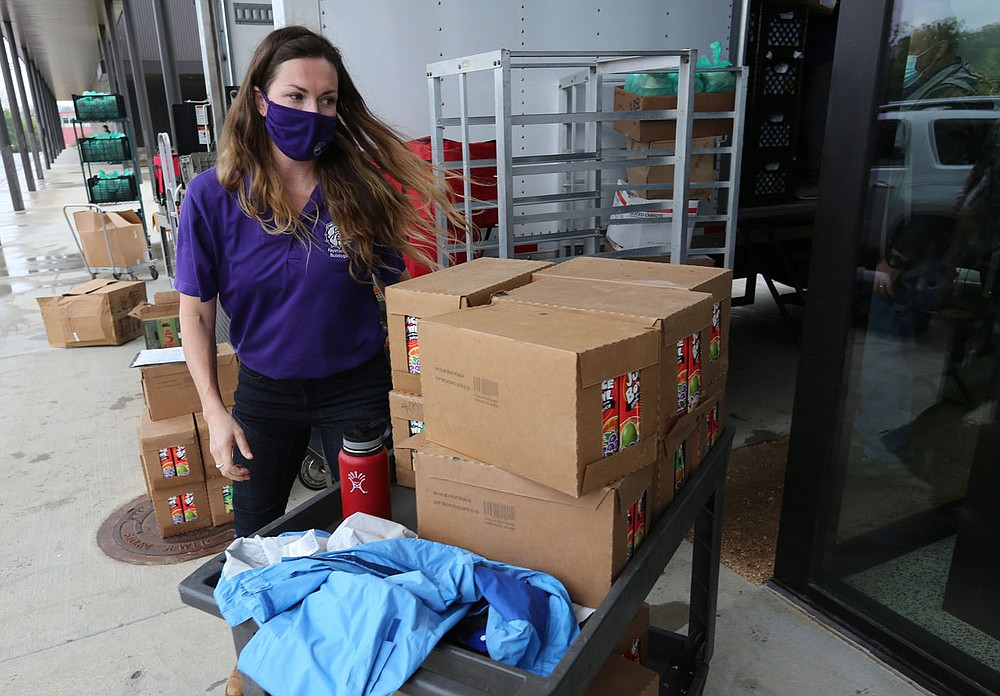Ally Mrachek, director of the child nutrition department for Fayetteville Public Schools, positions juice boxes Tuesday, September 22, 2020, as meals are loaded into vehicles during a curbside service at Fayetteville High School. The district distributed 10 meals each to 350 students. The meals are available to all students in the district. Check out nwaonline.com/200923Daily/ and nwadg.com/photos for a photo gallery. (NWA Democrat-Gazette/David Gottschalk)