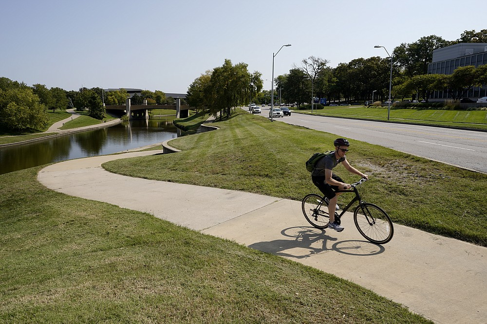 A cyclist rides a trail adjacent to Volker Road Thursday, Sept. 24, 2020, in Kansas City, Mo. The stretch of road, along with parts of two other streets, would be renamed to honor Rev. Martin Luther King Jr. under a city proposal coming in the wake of failed effort to honor King last year. (AP Photo/Charlie Riedel)